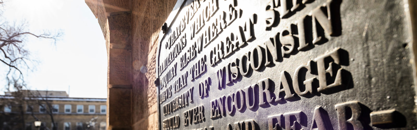 "Sun shines on the ""Sifting and Winnowing"" plaque on Bascom Hall"
