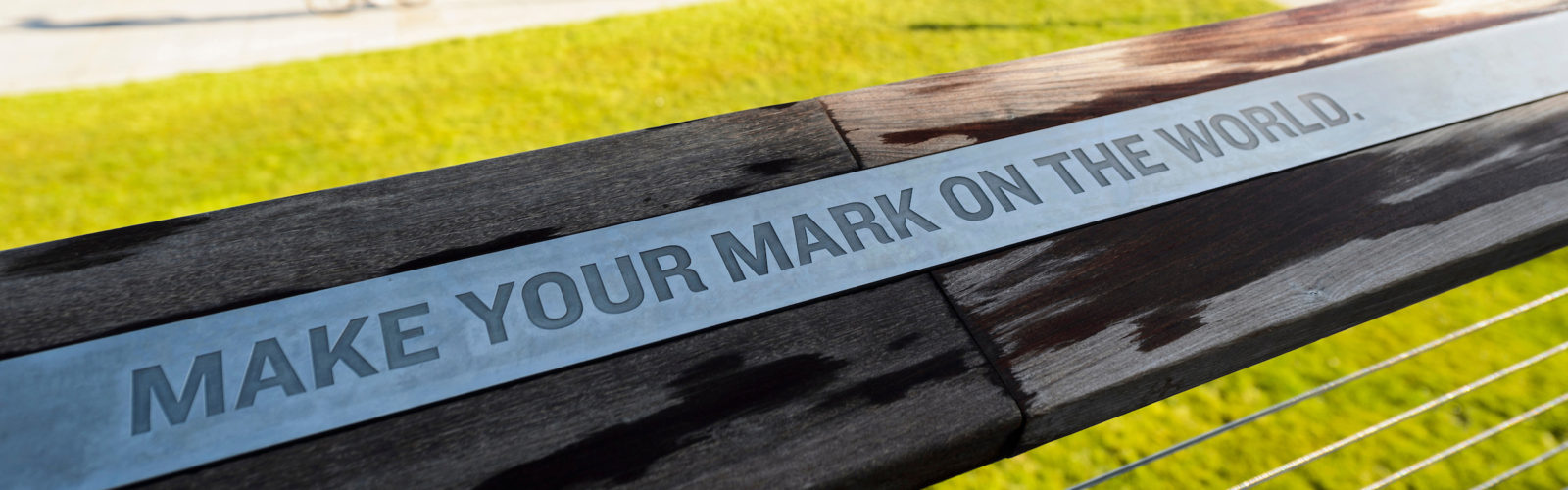 "Photo of a railing at Alumni Park engraved with the words ""Make Your Mark on the World"""